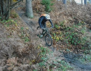 Rider going down a muddy ramp in Forest of Dean.