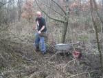 Trail builder filling wheel barrow with mud.