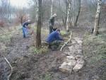 Three trail builders working on trail.