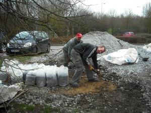 Volunteers loading gravel into bags.