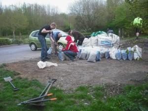 Volunteers loading gravel into sacks at mountain bike trail.