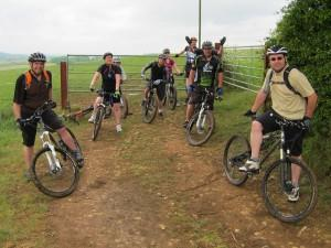 Group of mountain bikers standing by a gate.