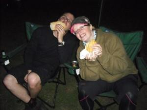 Two people stuffing their faces at a barbeque.