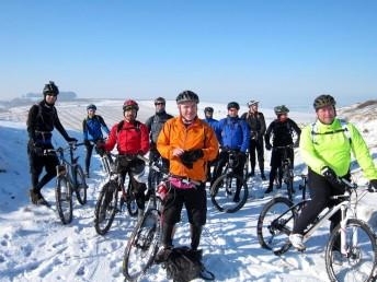 Group of mountain bikers near Barbury Castle in the snow.