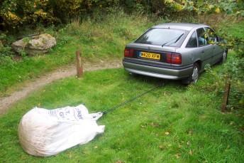 Car towing a gravel sack.