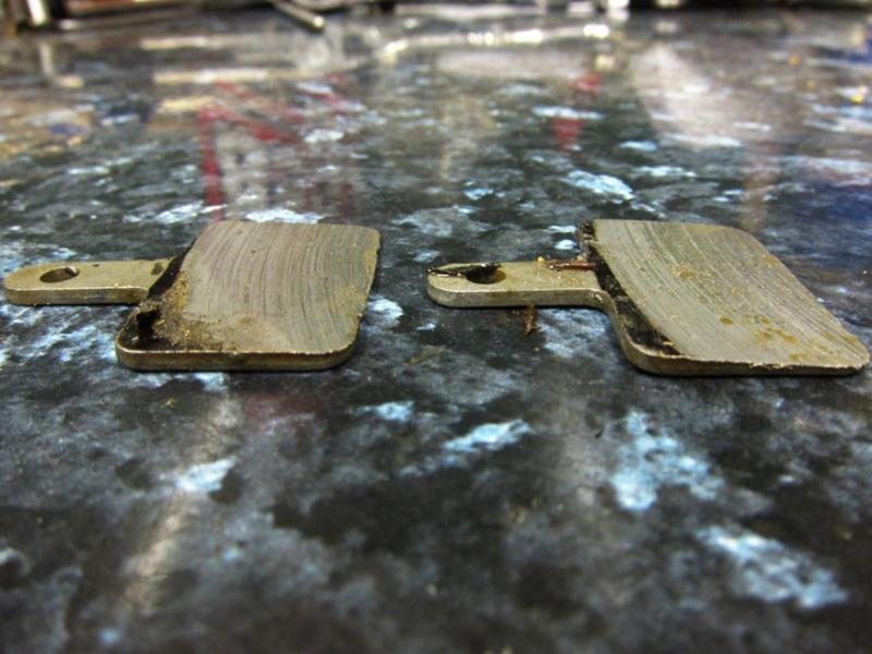 Bike brake pads worn down to the metal.