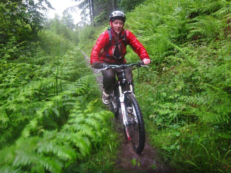 Wet mountain biker riding up a hill.